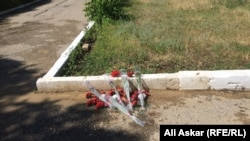 Цветы на месте гибели военнослужащих в день нападений подозревааемых боевиков в Актобе 5 июня 2016 года.