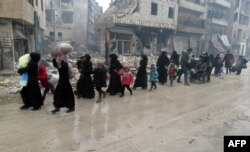 Syrian residents fleeing violence in the restive Bustan al-Qasr neighborhood arrive in Aleppo's Fardos neighborhood on December 13.
