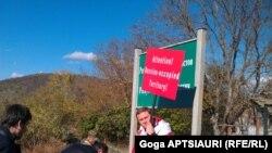 """საოკუპაციო ზოლის გასწვრივ მავთულხლართებთან ახალგაზრდებმა ორი ტრაფარეტი ჩაარჭვეს ქართულ-ინგლისური წარწერით: """"ყურადღება, რუსეთის მიერ ოკუპირებული ტერიტორია""""."""