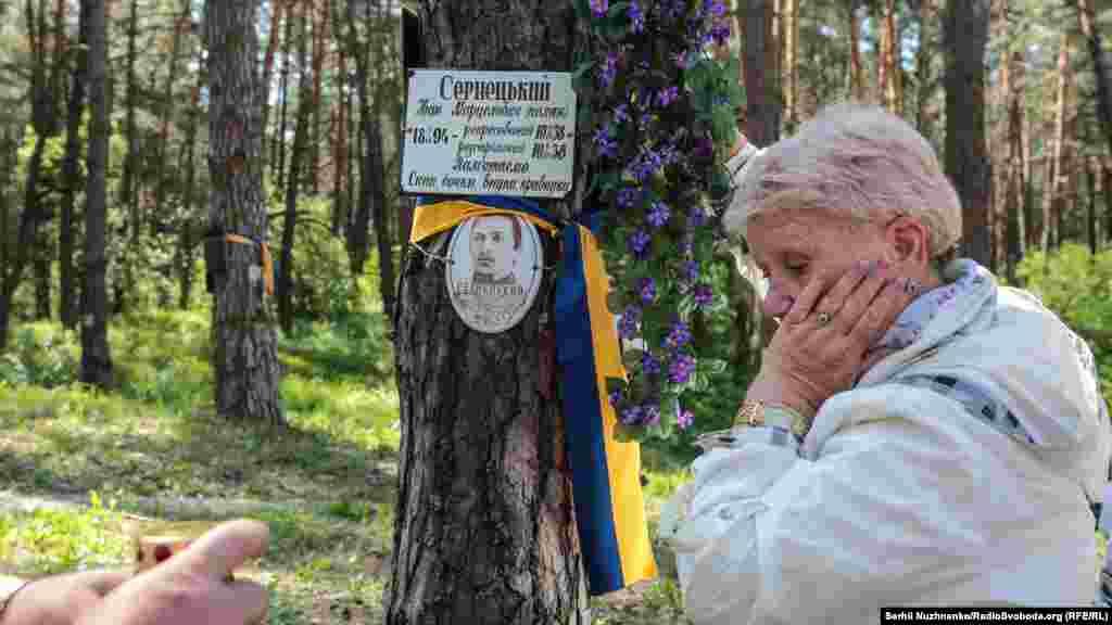 Онука Ольга Піддубна-Сарнецька біля таблички з прізвищем її діда.Лише в 2014 році сімя дізналась де місце розстрілу і поховання