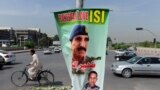 FILE: A cyclist rides past a banner bearing the image of former Inter-Services Intelligence (ISI) Chief Lt. General Zaheerul Islam in Islamabad, April 2014.