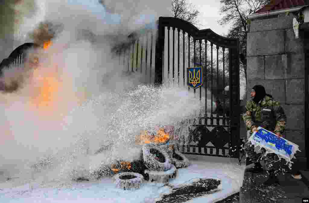 A serviceman from the volunteer battalion 'Aydar' throws a signboard over the gates, as burning tires are extinguished during a protest rally in front of Ukrainian Ministry of Defense in Kyiv, on February 2, 2015. (epa/Roman Pilipey)