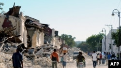 Locals walk in a destroyed street in Port-au-Prince