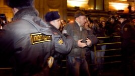 Police detain one of dozens of activists at a protest rally in central Moscow.