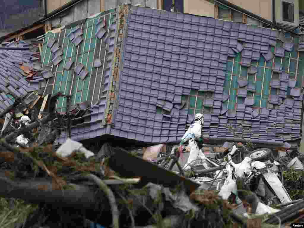 A Japanese police officer in a protective suit walks past a damaged house while searching for bodies in Minamisoma, about 18 kilometers from the damaged Fukushima nuclear power station on April 11. Photo by Kim Kyung-hoon for Reuters