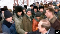 Putin shakes hands with workers during a visit to an oil and gas field in Surgut, Siberia, in March 2000.