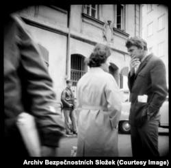 """Писатель Милан Кундера (справа) разговаривает с коллегой. В вышедшей в 2008 году книге под названием """"Прага через объектив спецслужб"""" – откуда взяты многие из этих фотографий – человек в кожаной куртке на заднем плане описан как агент с камерой, скрытой в портфеле. Камеру можно было привести в действие с помощью тонкого шнурка, то есть даже не прикасаясь к ней"""