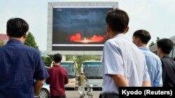 Люди смотрят репортаж о запуске баллистической ракеты «Хвасон-12». Пхеньян, КНДР, 30 августа 2017 года