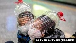 Disa djem mbajnë maska mbrojtëse, doreza dhe shishe uji të modifikuara në një karrocë në një aeroport në Kinë.