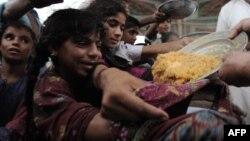 Pakistanda daşqından qaçanlara yemək paylanır.