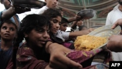 أطفال باكستانيون يتزاحمون للحصول على غذاء في أحد المخيمات بعد فيضانات 2010