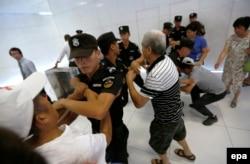MH370-ის ჩინელი მგზავრების ახლობლები ცდილობენ შეაღწიონ მალაიზიის ავიახაზების ოფისში, პეკინი.2015 წლის 5 აგვისტოს.