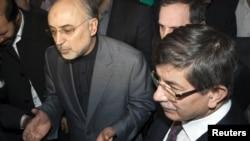 Iranian Foreign Minister Ali Akbar Salehi (left) with his Turkish counterpart, Ahmet Davutoglu, in Tehran on January 4.
