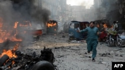 A Pakistani man runs past burning vehicles at the site of a bomb explosion in the busy Kissa Khwani market in Peshawar on September 29.