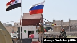 SYRIA -- A Russian soldier places the Russian national flag at the Abu Duhur crossing on the eastern edge of Idlib province, September 25, 2018