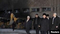 Нұрсұлтан Назарбаев (сол жақтан үшінші) өртеніп кеткен ғимараттың қасында жүр. Жаңаөзен. 22 желтоқсан, 2011 жыл.
