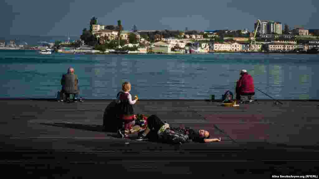 Містяни відпочивають на дерев'яному помості біля Севастопольської бухти