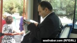 Türkmenistanyň awtobuslarynyň birinde gazet okaýan ýolagçy.