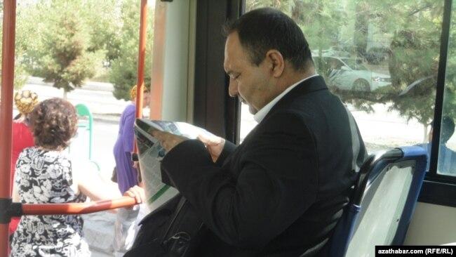 Человек читает газету в автобусе в Ашгабате. Иллюстративное фото.