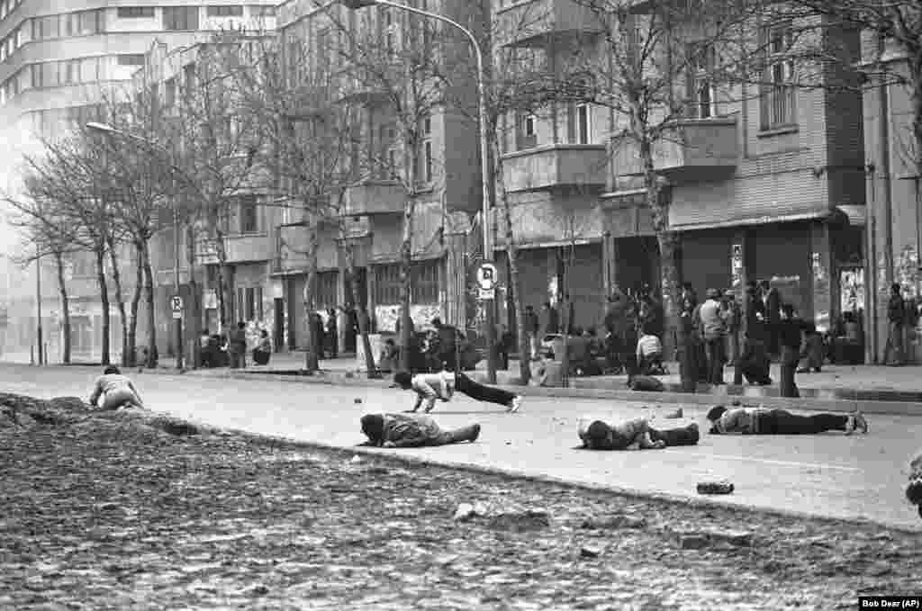 Severe clashes erupt on January 26, 1979 amid Iran's political instability and leadership vacuum. Antigovernment demonstrators dive for cover as Iranian army soldiers fire live rounds in Tehran.