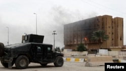 Smoke from previous clashes with Islamic State militants rises from a building near an Iraqi security forces military vehicle during an intensive security deployment in Ramadi, west of Baghdad, in December.