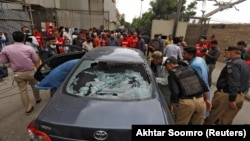 Police officers survey a damaged car at the site of an attack at the Pakistan Stock Exchange entrance in Karachi after a militant attack on June 29.