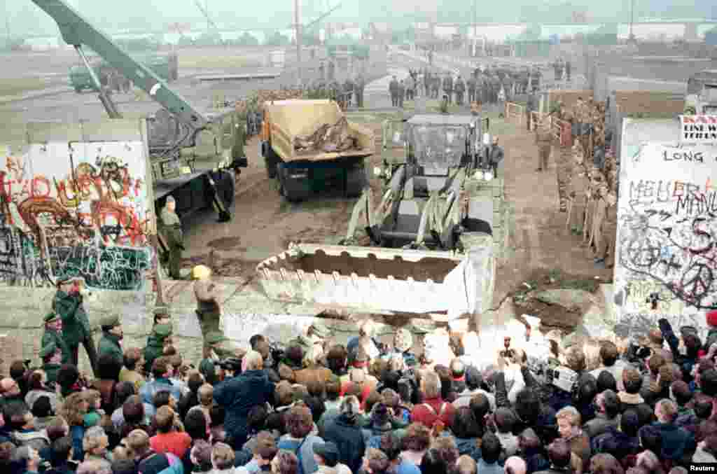 An East German bulldozer and crane knock down the Berlin Wall at Potsdamer Platz to make way for a new border crossing on November 12, 1989.