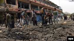 Afghan security officials inspect a crater left at the site after an attack by suspected militants at the Indian consulate in Jalalabad on March 2.