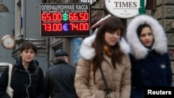 Люди идут рядом с пунктом обмена валют в Москве. 26 января 2015 года.