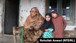 Reza Gul with her granddaughter Salima (center) whose father was killed five years ago.