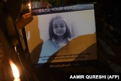 Pakistani civil society activists hold candles and a placard with an image of Zainab in Islamabad on January 11.