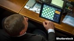 Депутат грає в шахи під час пленарного засідання парламенту