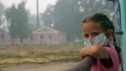 A girl wearing a protective mask looks out from her balcony in the village of Beloomut, near Moscow, during serious forest fires caused by a heat wave in 2010.