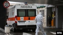 """Мъж в защитно облекло се насочва към входа на Института за спешна помощ """"Пирогов""""."""