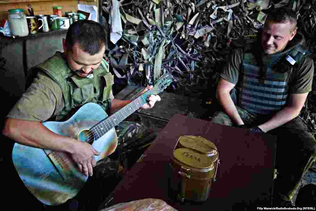 В період затишшя на лінії фронту бійці загону повітряних сил «Дика качка» грають улюблених пісень на гітарі