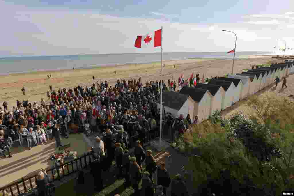 Family members of Canadian D-Day veterans, currently-serving soldiers, and local citizens attend a ceremony outside The Queen's Own Rifles of Canada House in Bernières-sur-Mer.
