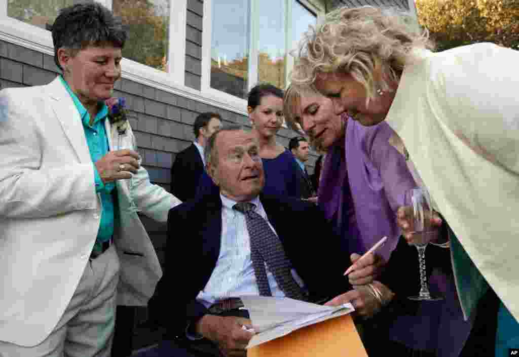 Former President George H.W. Bush (seated center) prepares to sign the marriage license of longtime friends Helen Thorgalsen (right) and Bonnie Clement (left) in Kennebunkport, Maine. Bush was an official witness at the same-sex wedding, his spokesman said. (AP/Susan Biddle)