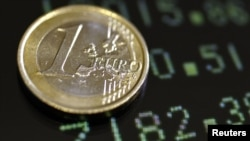 Italy -- A picture illustration shows a one euro coin on a flat screen displaying exchange rates in Rome, 08Dec2011