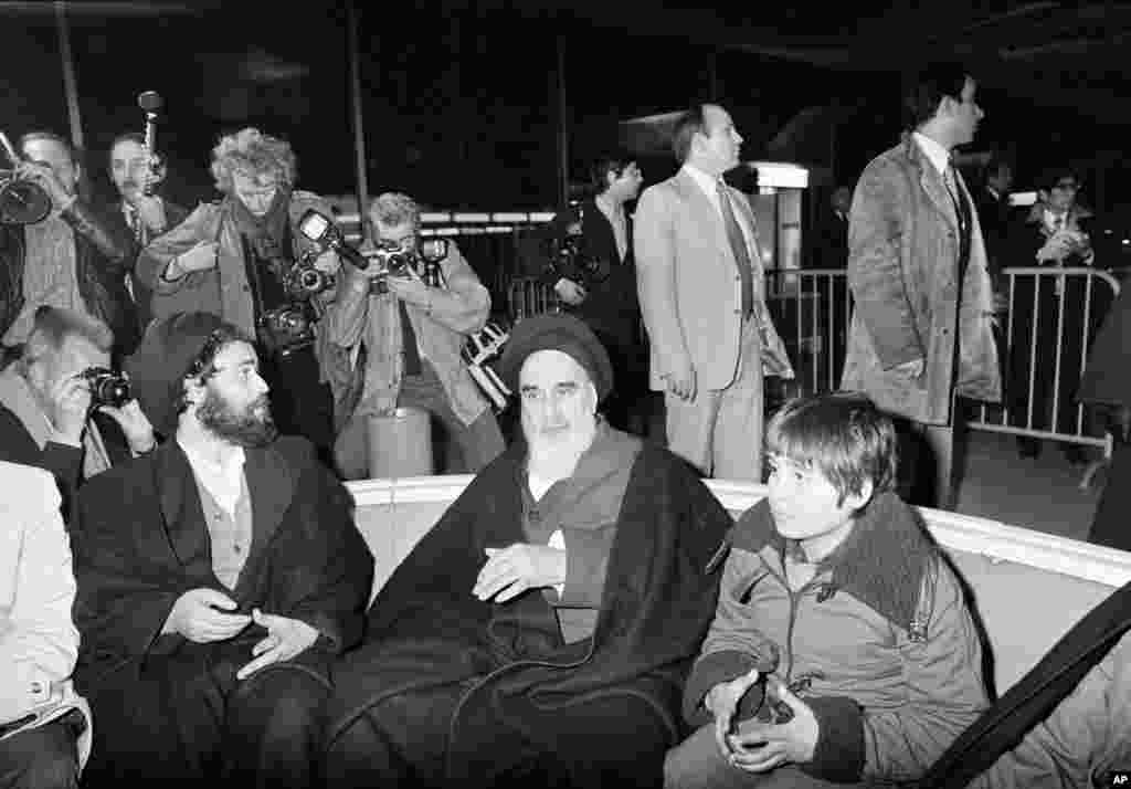 Khomeini talks briefly with reporters at Charles de Gaulle Airport in Paris, January 31, 1979, minutes before boarding a chartered airplane which was to fly him back to Iran after 14 years exile. His grandson is seen at his side.