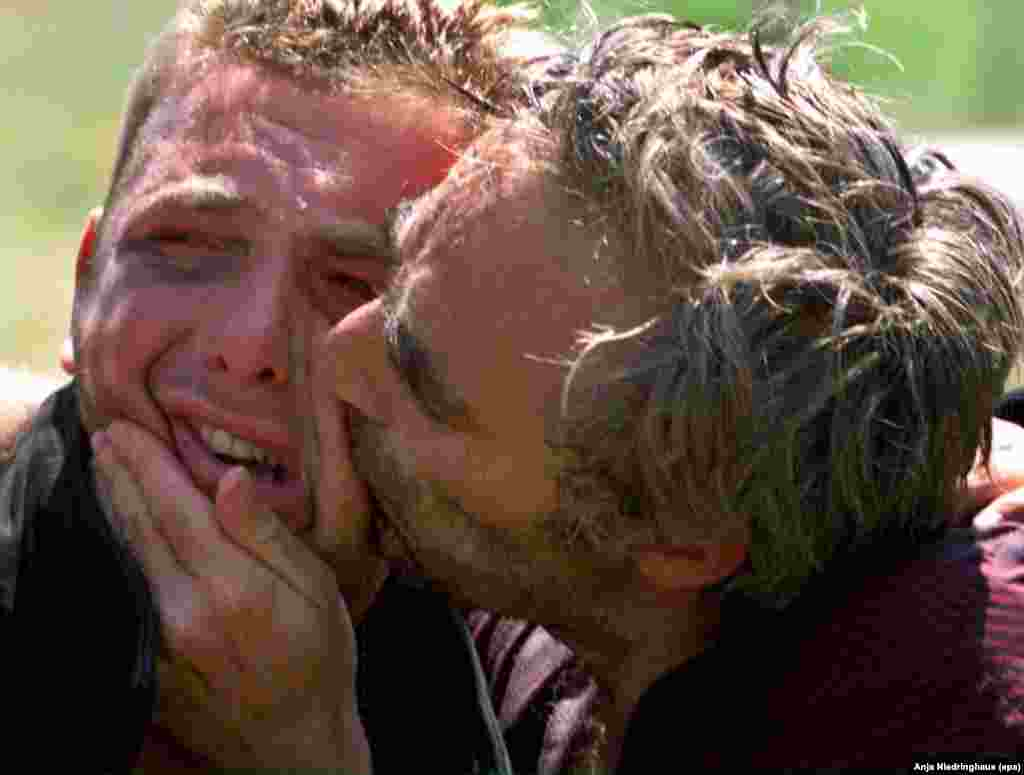 Kosovo Albanian refugees, released by Serb forces, are lost in tears as they kiss each other after reaching a checkpoint in Morina, Albania, on June 5, 1999.