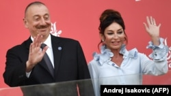 AZERBAIJAN -- Azerbaijani President Ilham Aliyev (L) and Azerbaijani First Lady and First Vice President Mehriban Aliyeva wave while standing on the podium after the Formula One Azerbaijan Grand Prix in Baku, June 25, 2017.