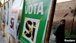 Мужчина проходит мимо плакатов, на лицевой стороне которых перечеркнута надпись: «Да». Плакаты размещены в Риме накануне референдума в Италии. 30 ноября 2016 года.