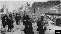 выжившие после бомбардировки идут по улице Нагасаки. Япония, август 1945