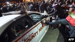 Протестующий атакуют полицейский автомобиль после вынесения судом присяжных решения по делу о смерти чернокожего юноши, застреленного полицейским. Фергюсон, 24 ноября 2014 года.