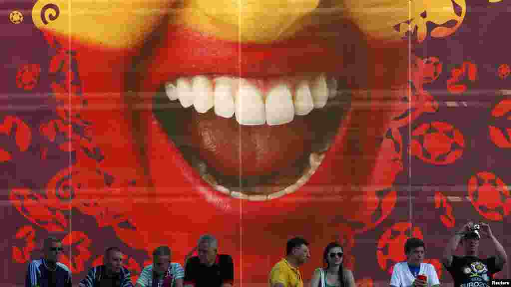 Soccer fans wait in front of a billboard depicting a face painted in the Spanish national colors before the start of the final.