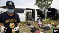 A police investigator gathers evidence at the scene of the massacre in Ampatuan.