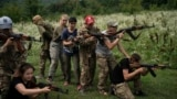 "Ukraine Nationalist Youth Camp-In this July 29, 2018 photo, young participants of the ""Temper of will"" summer camp, organized by the nationalist Svoboda party, practice tactical formations with AK-47 assault riffles in a village near Ternopil, Ukraine. (A"