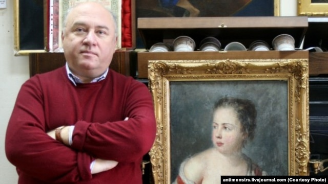 Russian art collector Aleksandr Khochinsky stands next to what Poland believes is the 18th-century painting Girl With A Dove.