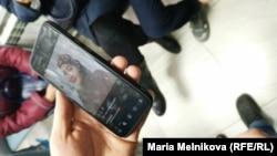 Полиция көлігі қаққан Лариса Бейсованың суретін ауруханаға оның жағдайын білуге келген туыстары смартфоннан көрсетіп тұр. Орал, 19 қараша 2019 жыл.