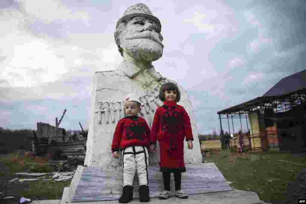 Kosovar children pose in front of a statue of Adem Jashari during a ceremony marking the 19th anniversary of the killing of the Kosovo Liberation Army (KLA) commander in Prekaz on March 7. (AFP/Armend Nimani)